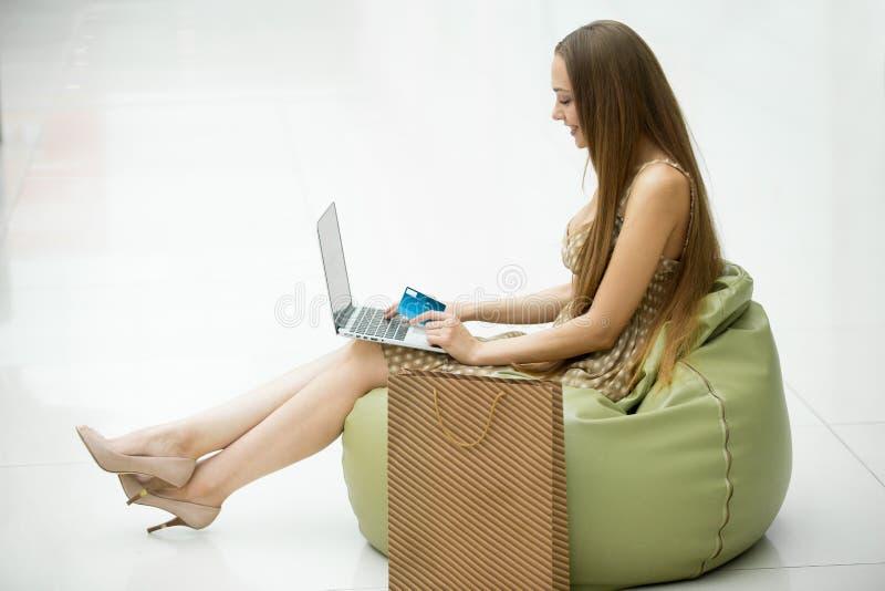 Zijaanzichtportret van vrouw met creditcard die laptop met behulp van stock foto's
