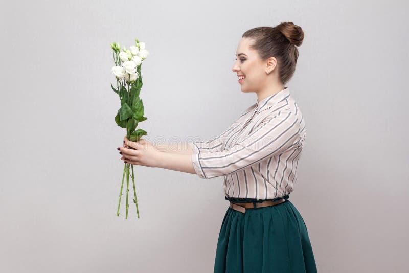 Zijaanzichtprofiel van aantrekkelijke romantische jonge vrouw in gestreept overhemd en het groene boeket van de rokholding van wi stock afbeelding