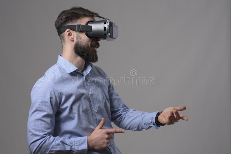 Zijaanzichtprofiel van de jonge volwassen gebaarde mens die vr van glazen genieten die met digitaal denkbeeldig wapen schieten stock foto