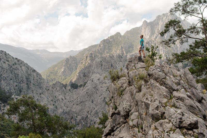 Zijaanzichtvrouw die zich op de rots op het mooie landschap bevinden stock fotografie