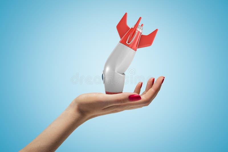 Zijclose-up die van de hand van de vrouw omhoog en kleine gebroken raketbovenkant - neer, op lichtblauwe gradiëntachtergrond onde royalty-vrije stock afbeelding