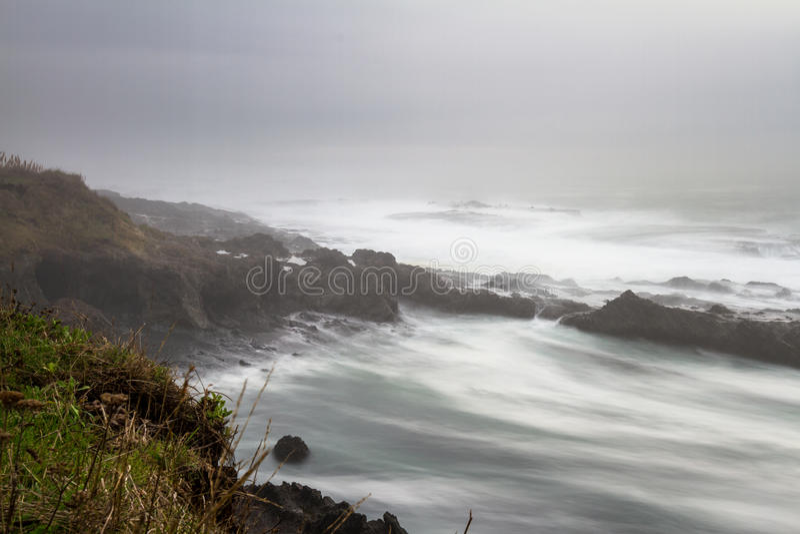 Zijdeachtige golven die op de rotsen verpletteren stock afbeelding