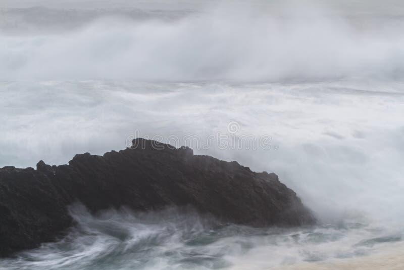 Zijdeachtige golven die op de rotsen verpletteren stock fotografie