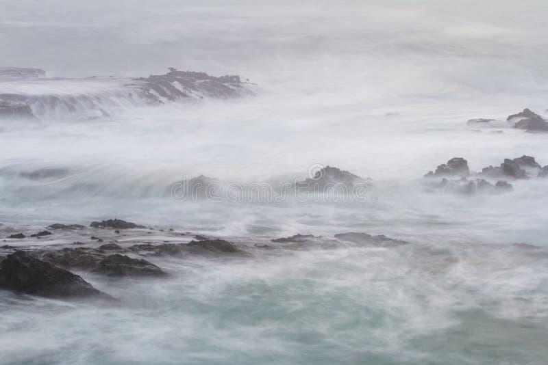 Zijdeachtige golven die op de rotsen verpletteren royalty-vrije stock foto's