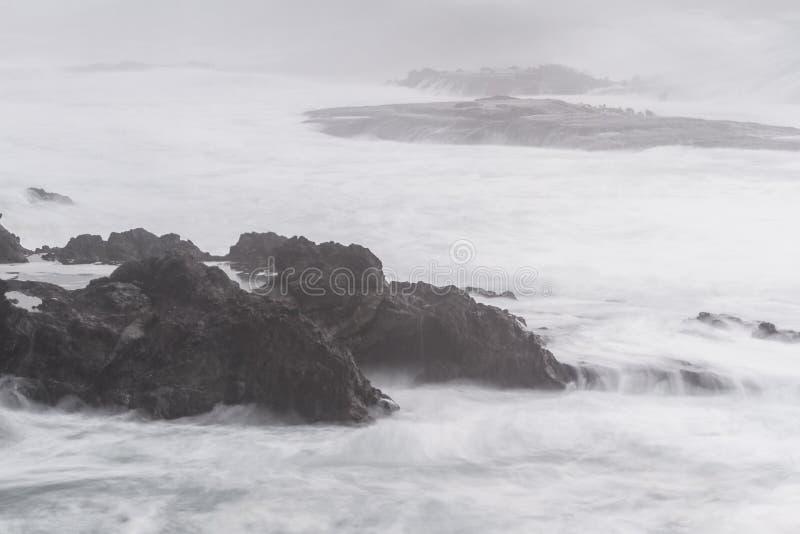 Zijdeachtige golven die op de rotsen verpletteren royalty-vrije stock afbeeldingen