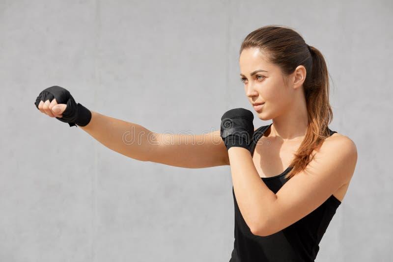 Zijdelings geschoten van aantrekkelijke sportieve vrouw heeft de bokser verbanden op handen, praktijken in dozen doen, klaar aan  royalty-vrije stock foto's