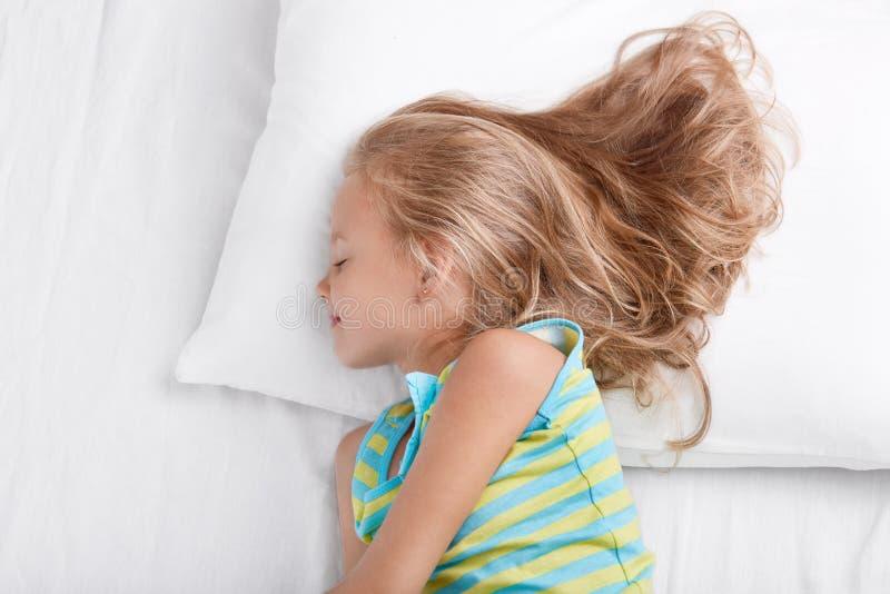 Zijdelings geschoten van klein jong geitje draagt nachthemden, die diep in slaap, rust bij bed, ligt op wit bed, geniet van bedti stock fotografie