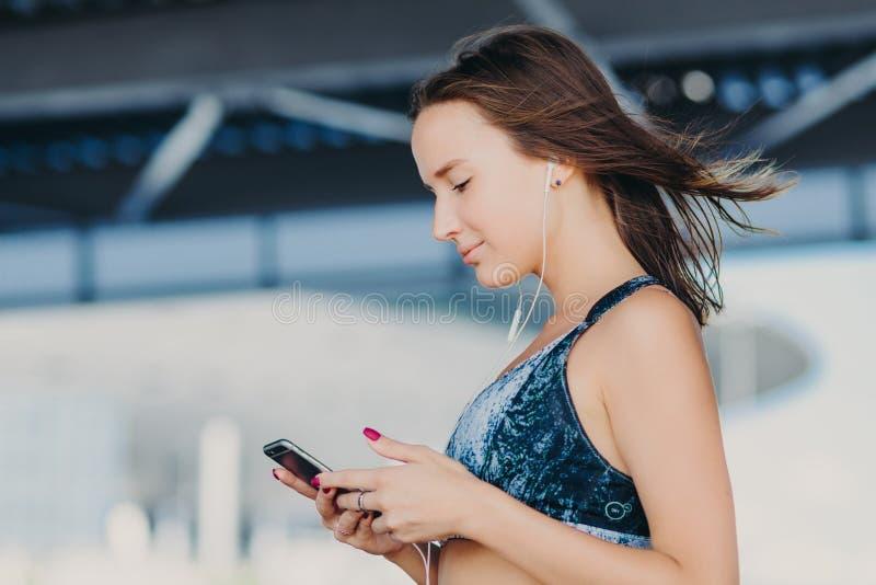 Zijdelings geschoten van sportief mooi wijfje met donker haar, gekleed in toevallige uitrusting, houdt moderne slimme telefoon, c royalty-vrije stock foto