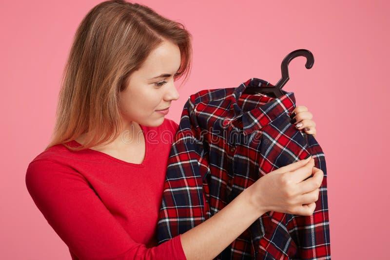 Zijdelings kiest het portret van prettig kijkend jong wijfje nieuwe uitrusting, kijkt op geruit chemise op hangers, verheugt zich stock foto's