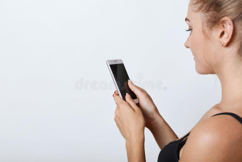 Zijdelings portret die van wijfje met gezonde zuivere huid die mobiele telefoon in handen met het lege scherm houden, nieuws leze stock afbeeldingen