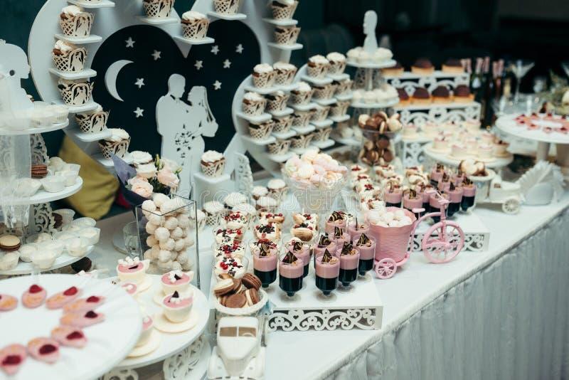 Zijdieschot van de bar van het huwelijkssuikergoed met verschillende heerlijke desserts zoals cupcakes, mararons, suikergoed word stock fotografie
