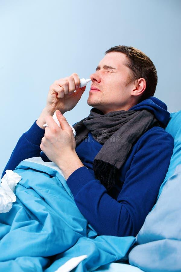Zijfoto van ziek donkerbruin mannetje die neusnevel gebruiken terwijl het liggen in bed stock afbeelding