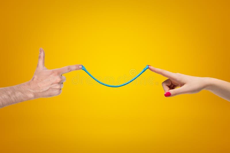 Zijgewassenclose-up van vrouw en man handen die vingers richten die aan elkaar, door dunne strook van blauwe kleverig wordt verbo royalty-vrije stock foto
