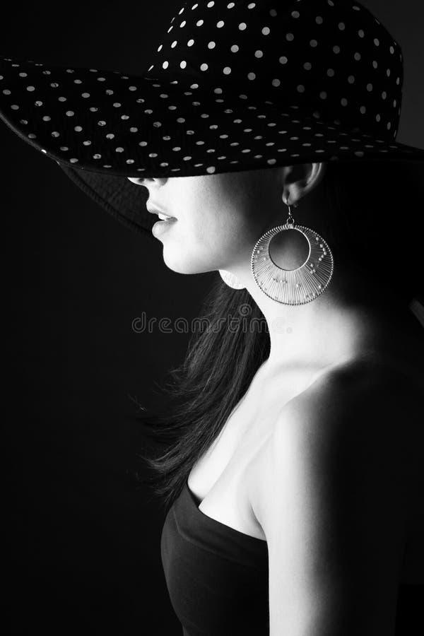 Zijgezicht van jonge vrouw in zwarte hoed met punten en met modieuze oorring royalty-vrije stock afbeeldingen