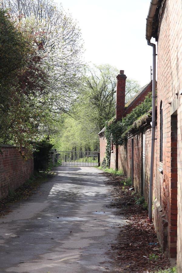 Zijhoek van oude landbouwbedrijfgebouwen op een weg van het land stock foto