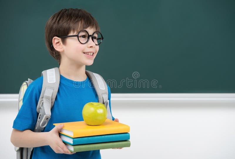 Zijn eerste dag op school. Vrolijk weinig schooljongen die B houden stock afbeelding
