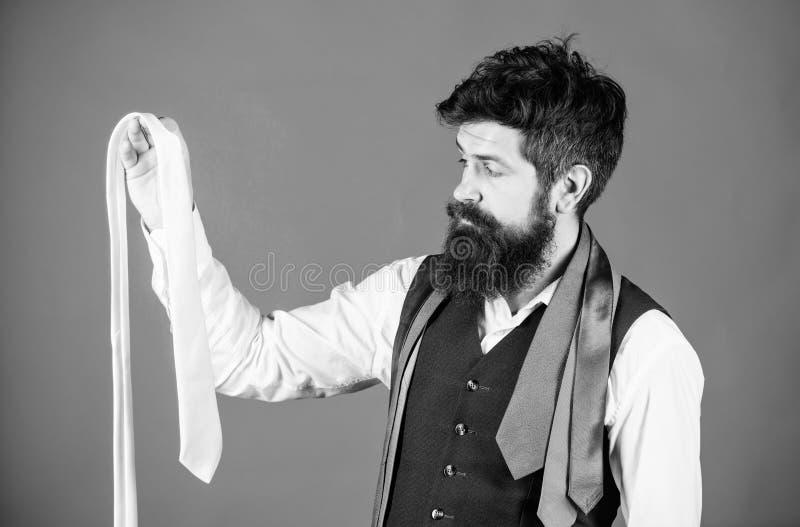 Zijn garderobe stelt zijn stijlbetekenis voor Gebaarde mens die een stropdas kiezen van zijn garderobe De garderobe van modieuze  royalty-vrije stock afbeelding