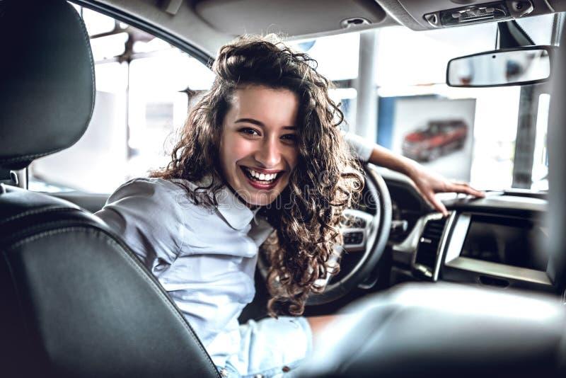 Zijn mijn nieuwe auto! Portret van mooie jonge vrouw binnen in nieuwe auto stock foto