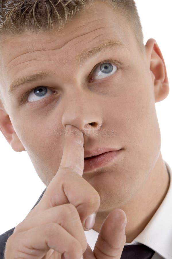 Zijn neus plukt en mens die stijgend kijkt royalty-vrije stock afbeelding