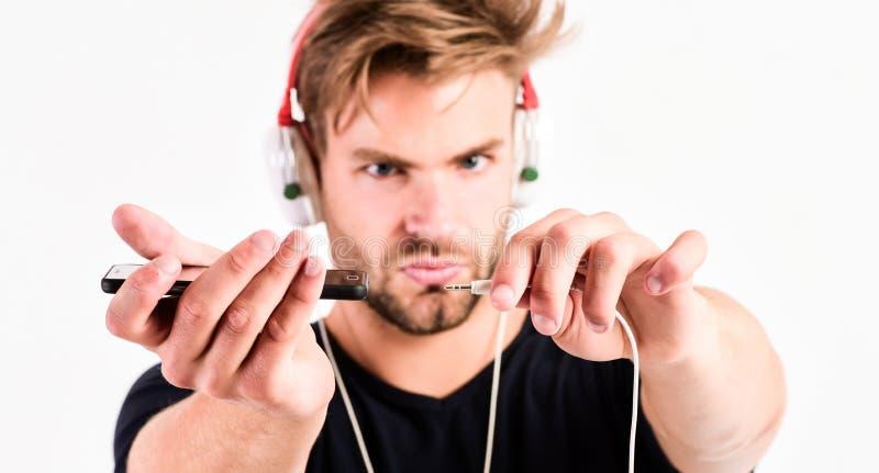 Zijn nieuwe hoofdtelefoons ebook en online onderwijs Muziekonderwijs de sexy spiermens luistert ebook Mens in oortelefoons stock foto