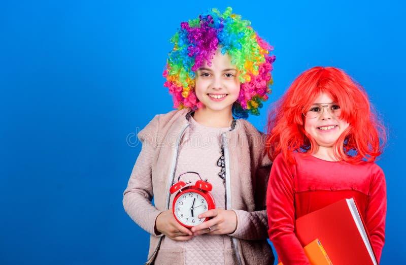 Zijn tijd te vieren Meisjes die gekke pruiken dragen die naar partijnacht gaan Leuke kinderen die met buitensporig haar wachten o royalty-vrije stock afbeelding