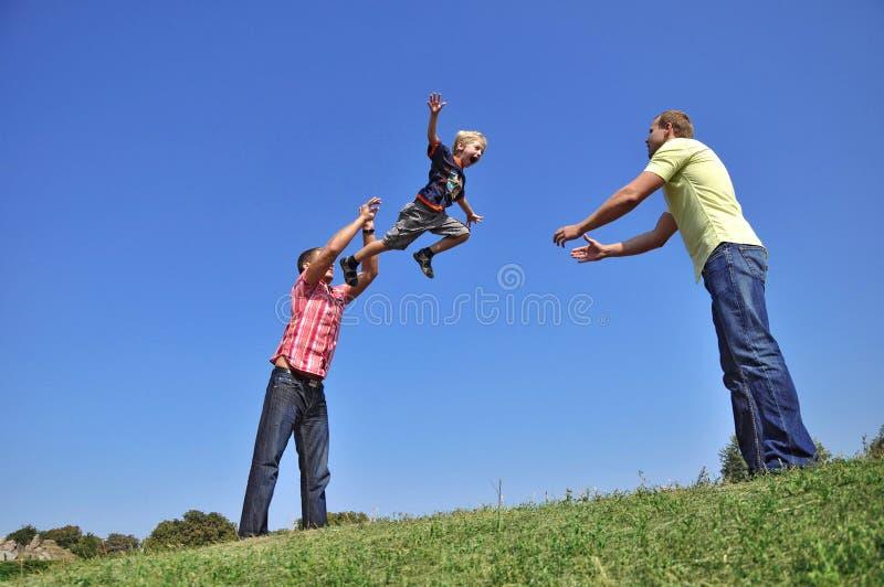 Zijn zoon in de lucht werpt en vader die hallo vangt royalty-vrije stock fotografie