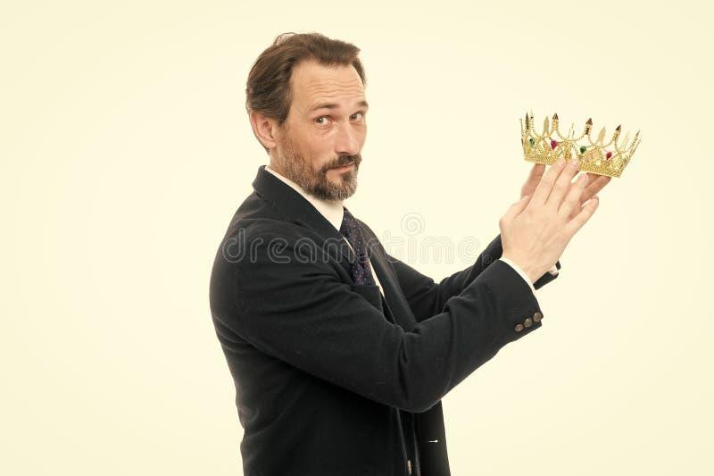 Zijnd succesvol De rijpe kroon van de zakenmanholding Zekere zakenman in kroon status ge?soleerd op grijs met zijn gekruiste wape stock foto