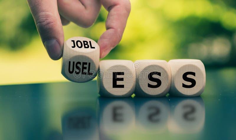 Zijnd werkloos en voelend nutteloos De hand draait een kubus en verandert het woord stock fotografie