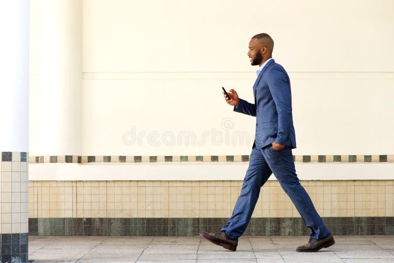Zijportret van de jonge Afrikaanse bedrijfsmens die met mobiele telefoon lopen royalty-vrije stock foto's