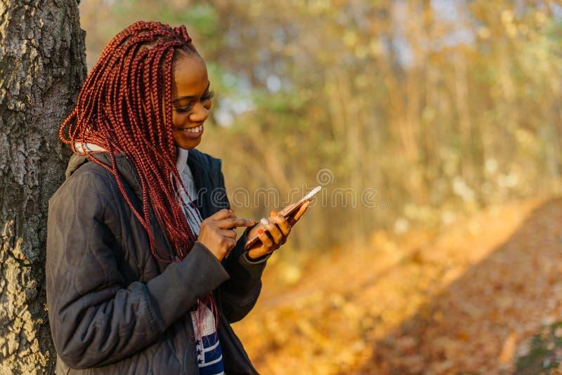 Zijportret van de jongelui die Afrikaanse dame met rood haar en mooie glimlach charmeren die, en op doorbladeren texting babbelen stock foto's