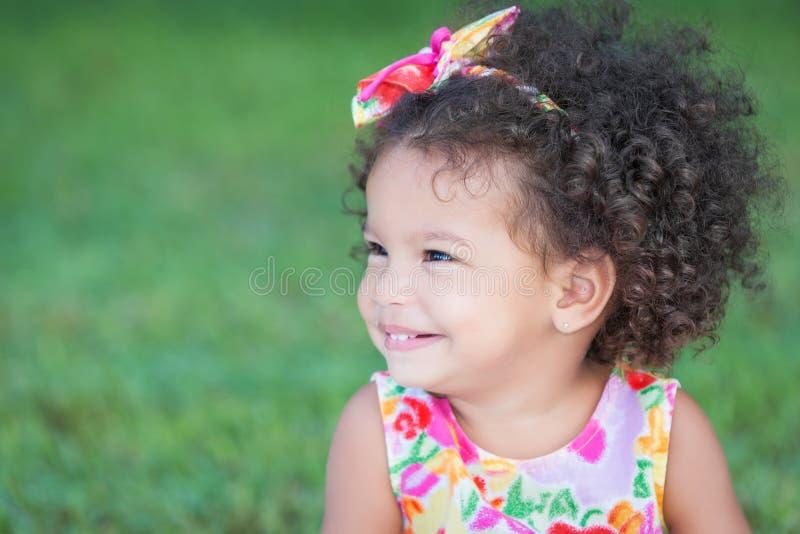 Zijportret van een klein Spaans meisje met een afrokapsel royalty-vrije stock fotografie