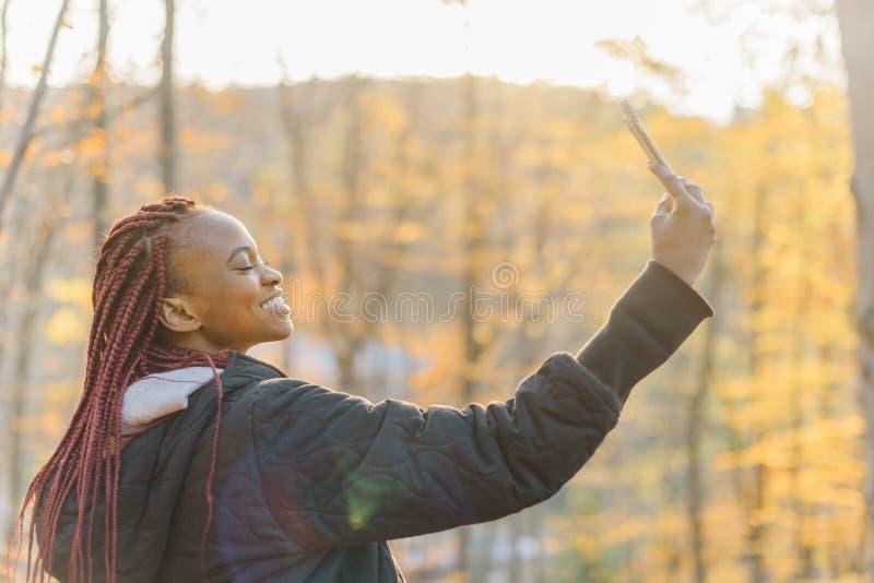Zijportret van het mooie Afrikaanse meisje met mooie glimlach die selfie op de mobiele telefoon in de herfstpark nemen royalty-vrije stock foto