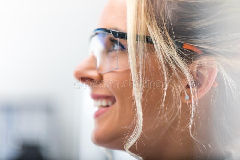 Zijportret van jonge aantrekkelijke vrouw in beschermende oogglazen stock foto