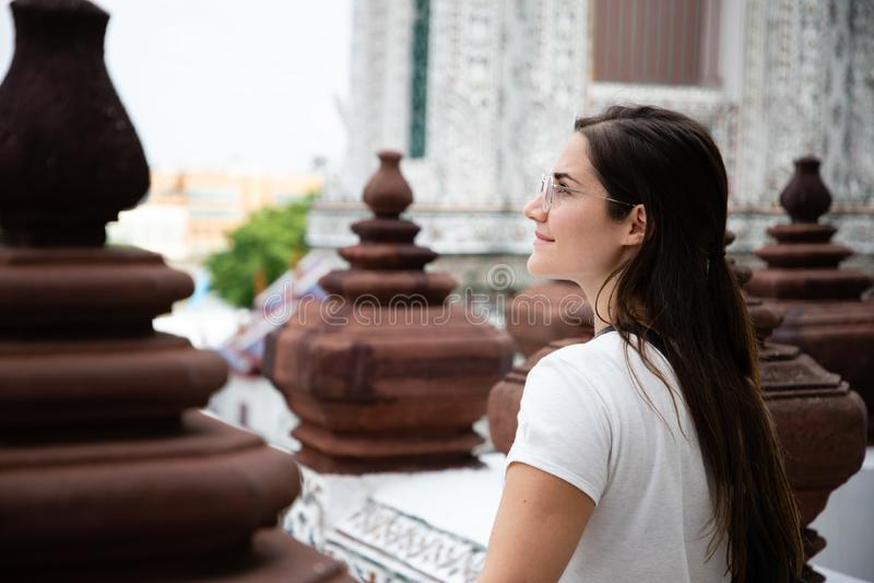 Zijportret van mooie vrouw met bruin lang haar tussen de Thaise kolommen van de tempeldecoratie royalty-vrije stock foto