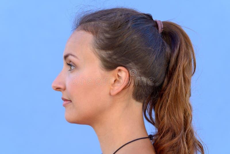 Zijportret van vrij jonge donkerbruine vrouw royalty-vrije stock afbeeldingen