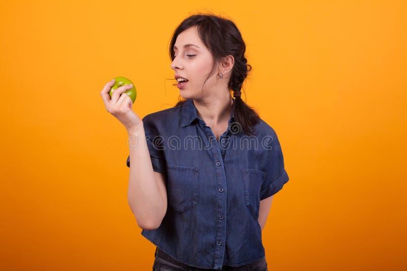 Zijportret van vrolijke jonge vrouw holding en het bekijken een groene appel in studio over gele achtergrond royalty-vrije stock afbeelding