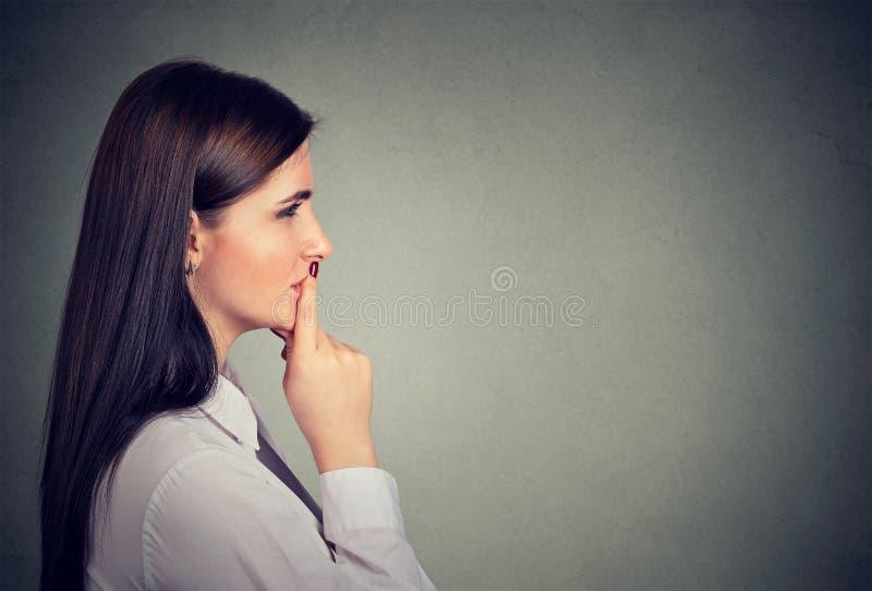 Zijprofiel van een nadenkende jonge vrouw stock afbeelding