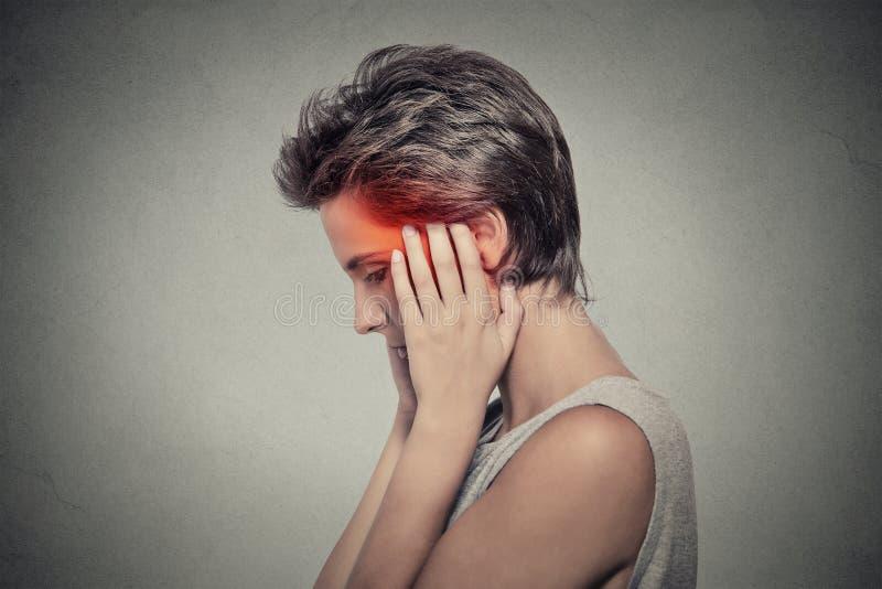 Zijprofiel zieke vrouwelijk hebbend de hoofdpijn van de oorpijn oorsuizing stock foto's