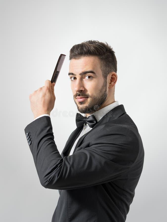 Zijprofielmening van de jonge mens die haar kammen die camera bekijken royalty-vrije stock foto