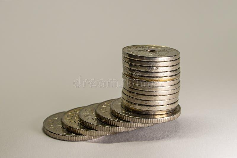 Zilver gekleurde die muntstukken op een lijst worden gestapeld stock fotografie
