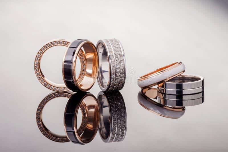 Zilver, goud, platinaringen van verschillende stijlen op de grijze achtergrond van bezinningen stock afbeeldingen