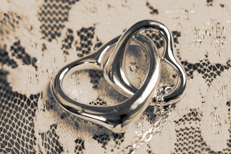 Zilver in verband gebrachte harthalsband met ketting op een achtergrond van de kantstof stock foto