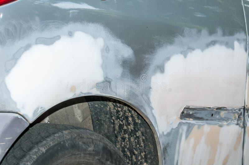 Zilveren auto met beschadigde verf en gedeukt metaallichaam van neerstortingsongeval met onvolledige carrosserie over gebarsten e royalty-vrije stock afbeeldingen
