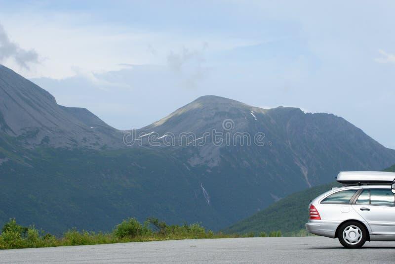 Zilveren auto met carrier in de bergen stock fotografie