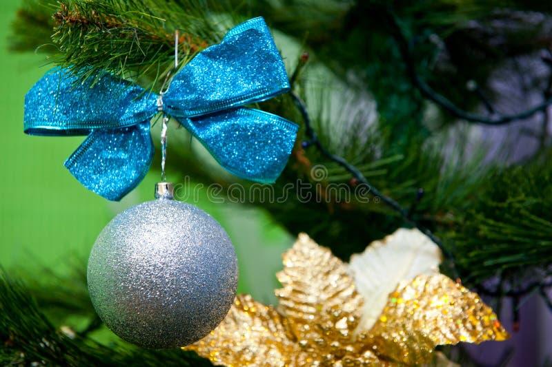 Zilveren baldecoratie met een blauwe boog voor een Kerstboom stock foto