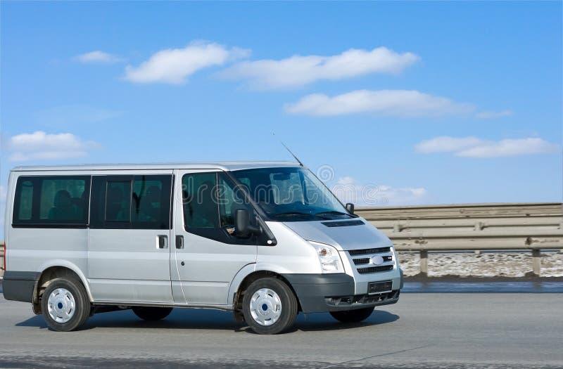 Zilveren bestelwagen op weg met blauwe horizon stock foto's