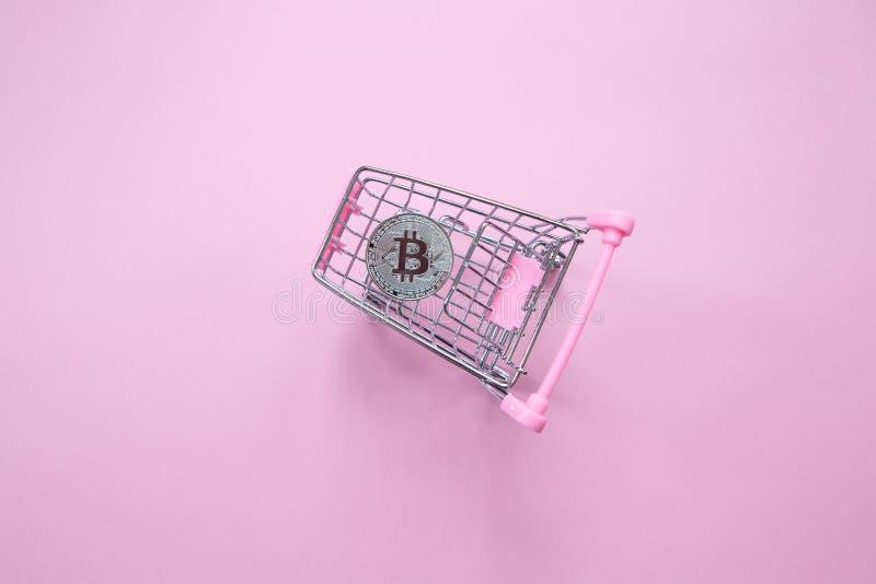 Zilveren bitcoin in boodschappenwagentje op een millennial roze achtergrond Hoogste mening minimalism Horizontale richtlijn Vlak  royalty-vrije stock fotografie