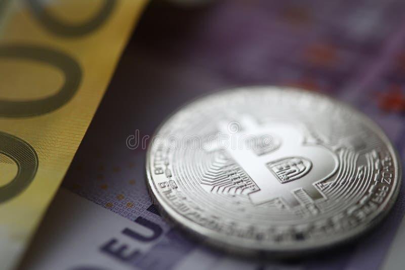 Zilveren bitcoin met euro contant geld ligt op de lijst royalty-vrije stock afbeelding