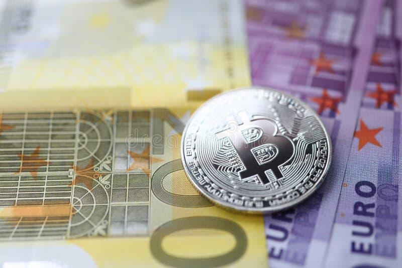 Zilveren bitcoin met euro contant geld ligt op de lijst stock fotografie