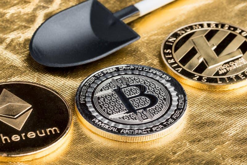 Zilveren bitcoins, litecoin, ethereumcrypto muntstuk met zwarte schop royalty-vrije stock foto